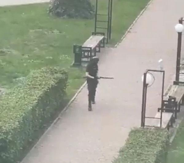 全身黑衣的男子,持枪在校园里走动。