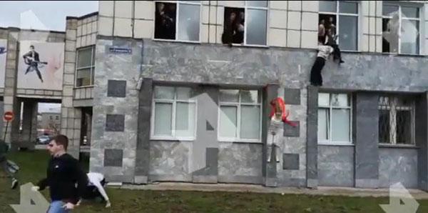 学生爬窗逃命往下跳,跳到绿色草坪上。