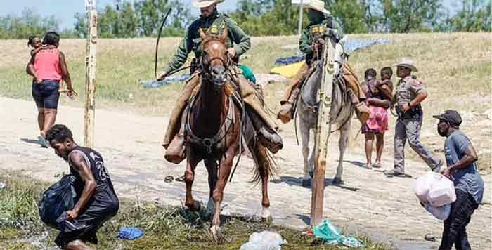美国边境执法员骑马向移民挥鞭的画面。