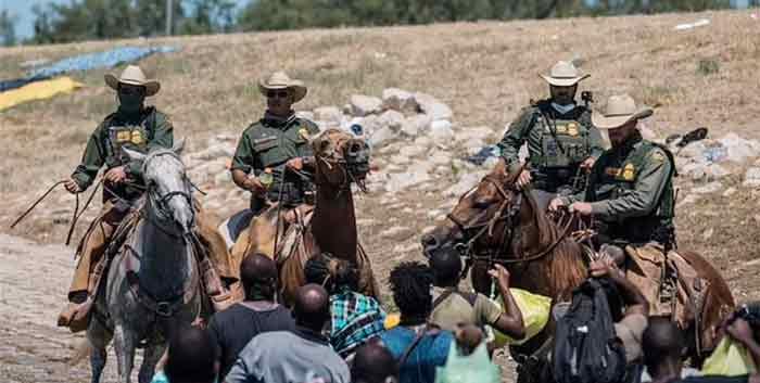 在边境骑马挥鞭执法的CBP人员。