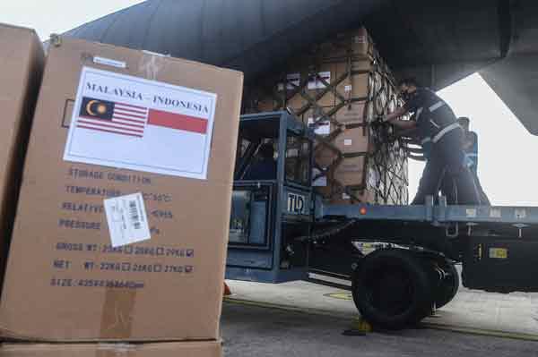 空军将我国赠送给印尼的物资搬到运输机上。
