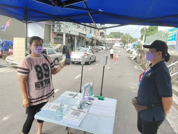 志愿警卫队队员林女士(右)检查民众吴玉花的电子疫苗接种证书。